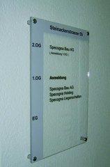 Plexitafel beschriftet mit Systemtext und mit Abstandshalter an Wand montiert
